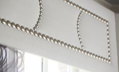Simple and contemporary white cornice aka padded balance which studs aka upholstery nails