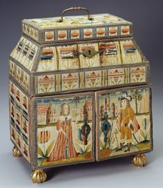 This casket or small cabinet is covered with long stitch needlework in silk, with a scene of figures in a landscape on the top, which opens, and a figure on each of the doors. The cabinet opens in three places and includes divisions, recesses, drawers and hidden compartments, and contains several small articles. Needlework caskets such as these were used for a variety of purposes and frequently contained receptacles for ink and sand, bottles for perfumes and sections for combs and…