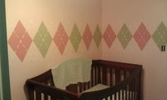 Argyle nursery wall - Pink accent wall with darker pink diamonds and tan diamonds that are the same color as the rest of the room.