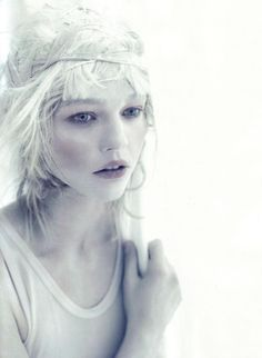 Sasha Pivovarova by ©Paolo Roversi for Vogue Italia April 2010. Featured in low saturation with light color eyes and a pink lip, slightly revealed front teeth, gripping her left shoulder with her right (opposite) hand. She adorns a woven headband and simple shirt matching in grey (or) ivory color.