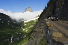 Cars on Going to the Sun Road through mountainside tunnel, low clouds in valley, Glacier National Park, Montana, USA.