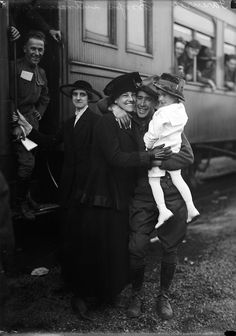 A soldier is reunited with his wife and child, c. 1918.