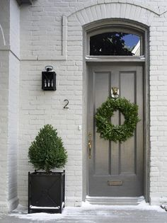 Simple. Elegant. Welcoming. I love the two tones of grey in the exterior, a touch of black in the lantern and a pop of color and life with the greenery. Gives me ideas...