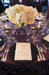 Purple linens, embellished with crystals and flowers, are topped with white arrangements of hydrangeas and orchids.