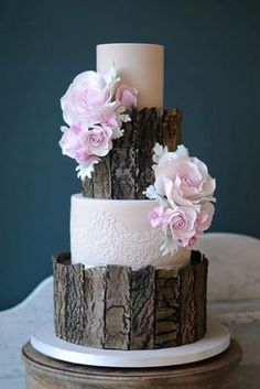 A woodland themed wedding cake - love the elegant mix of the white lace pattern with the wood. #OutdoorWedding #WeddingCake