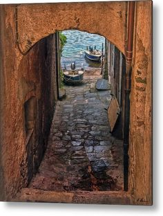 This narrow areaway alley between two houses on the Island San Giulio, in Italy, takes the residents right away to their boats on Lake Orta  -  Photo by Hanny Heim Snowbird Photography #italy #italien #architecure #isolasangiulio #boats