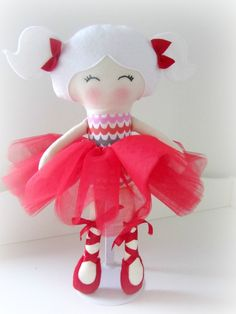 Handmade doll made using designer cottons, 100% wool felt, and filled with soft polyester filling. This ballerina has white hair, a removable soft red tulle tutu and sewn on ballet shoes with satin ribbon. Her face has been hand embroidered and she stands at 40cm tall. She is CE marked so safe for children and suitable from birth.