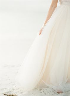 Whether your skirt is elaborate or simple tulle, it should get its own moment. Bonus points if you're getting married on the beach like this bride and can achieve a stunning monochromatic palette.  Photo by KT Merry Photography via Style Me Pretty