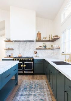 Green/blue colored cabinets kitchen by Amber Interiors. It's easy to go wrong with colored cabinets, but this kitchen is done absolutely right. The way Amber paired the cabinet color with the marble, white and natural wood is perfection.