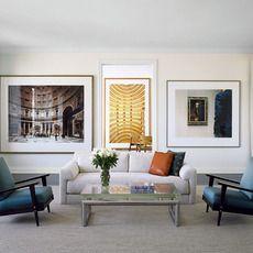 ゆったりと置かれたソファ。ダイニングへの入口を通して見える絵画は計算された大きさになっていて、3つの絵画が並んで見えるギャラリーのようなリビングです。