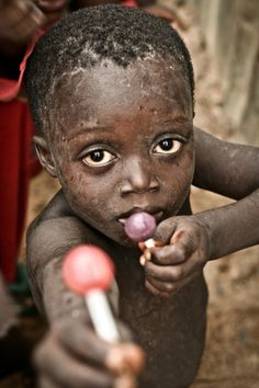 The world can learn alot from this photo. This child has nothing, including not even enough food, but the child is offering a sucker to the camera person. This has got to be one of the most heart warming photos I've ever seen ♥ Photo by Emil Leonardi - Sierra Leone, 2010.