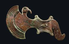Elamite bronze axe head, late 3rd-early 2nd millenium B.C.  The crescentic blade decorated with ribs, a bird head emerging from the top edge, the blade incised on either side with a lion attacking a deer, the concave shaft with ribbing around the edges, a lozenge on each side decorating the attachment pin and a protruding beak-like protome, 16 cm long. Private collection