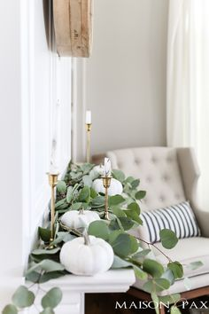 silver dollar eucalyptus and white pumpkins and brass candlesticks make elegant neutral fall decor Fall decor with white pumpkins and neutral textures gives a subtle fall look. Don't miss these fall decorating tips and ideas for creating a cozy home.