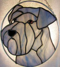 Handmade miniature schnauzer stained glass suncatcher portrait. It measures 7 X 8 inches in diameter and comes with an attached chain for hanging.