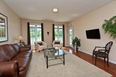 The Rosedale.  Living room.  Transoms, carpet, area rug, leather couch, hardwood, tv on wall, tub chairs, white leather chairs, glass tables....www.qualityhomes.ca