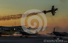 Photo about Aircraft show in the sunset sky with smoky long trail. Plain flying over other plains on the ground. Image of artistic, cargo, land - 98725979 Sunset Sky, Air Show, Airplanes, Trail, Aircraft, Clouds, Artist, Image, Planes