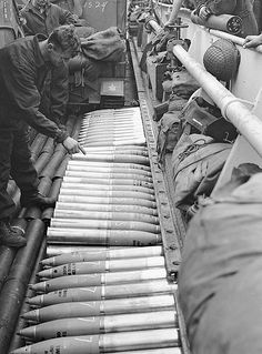 Lance-Bombardier Walter Cooper, 14th Field Regiment, Royal Canadian Artillery (R.C.A.), aboard a Landing Ship Tank counting out 105mm. shells which will be fired on D-Day. Southampton, England, 4 June 1944