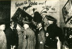 "Adolf Hitler visiting the ""Dada Wall"" in the Entartete kunst exhibition.  Note that the paintings have been tilted."