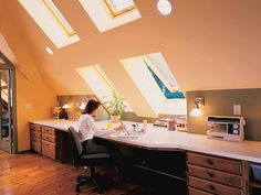 The intersection between the sharply pitched ceiling and the low wall of this attic provides a perfect spot for a long built-in desk that functions as a craft center. Large, operable skylights that double as windows fill the area with natural light, making it perfect for detail work. (Photo: Photo: johngranen.com; Designer: Gary Epstein)