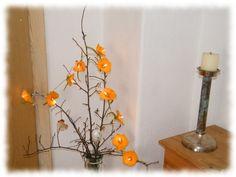 .    An einer weißen Lichterrkette mit Schalter ranken sich 10 gelbe Blüten. Jede einzelne Blüte hat einen orangefarbenen Tupfen in der Mitte und e...