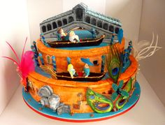 """Two tier Venetian Extravaganza Cake. This cake features four pastillage masks, with feathers and beads and a replica Rialto bridge, also made from Pastillage. The commissioning family are having a lovely time in their gondolas. Each tier has been """"painted"""" with royal icing and edible powders to recreate the plastered exteriors of the Venetian buildings. The Lion of St Mark (also the birthday boy's name) is featured on the front of the cake."""
