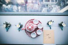 An overhead shot of an oriental tea set and posies with white flowers on a windowsill