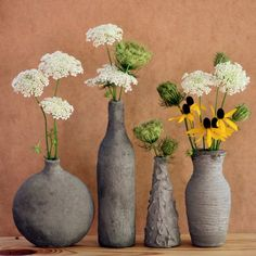 The vases are made by covering inexpensive glass vases or bottles from the recycle bin with anchoring cement.