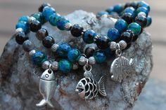 You get exactly whats in the picture, all my jewelry is one of a kind. - THREE BRACELET STACK - you are purchasing THREE bracelets that come together! - Blue/green chrysocolla 6mm acrylic beads. - Black agate 6mm stone beads. - Three silver tone fish charms. - Silver tone accents. - 6.5 Inches un-stretched (approximately). These bracelets best fit people with a small/medium frame. - Ships from Canada.  Bracelet stacks are all the rage - but why go through all the trouble of looking for…