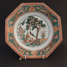 A Kangxi Famille Verte porcelain dish c.1690 – 1720. Decorated in strong Famille Verte enamel colours with a creeper growing up a pine tree with birds in a terraced garden. The border of this European shaped porcelain dish shows phoenix and peony against a seeded ground. The gadrooned rim is picked out in Rouge de Fer and gilt.