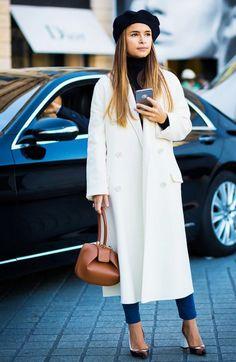 Miroslava Duma wears a turtleneck, white coat, cropped pants, block heels, a top-handle bag, and a black beret