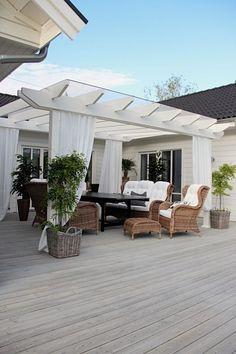 charming white deck pergola with wicker furniture More