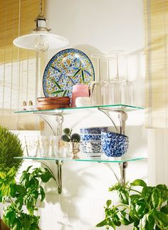 Open glass shelving with mixed pattern dishes on display in bright white kitchen.