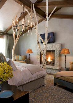 Gemütliches Schlafzimmer im Landhausstil mit Feuer im Kamin und Birken Baumstamm, Stehlampe orange