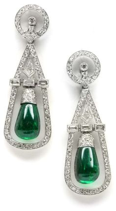 Art Deco emerald and diamond earrings by Cartier, circa 1935. Each earring is hung with a polished emerald within an open diamond-set frame. The frames are each divided by a line of baguette diamonds and with fancy kite shaped diamond, from diamond set circle-and-dot tops, millegrain set. Via Diamonds in the Library.