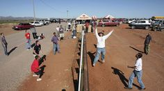 """Residents of Naco, Arizona join residents of Naco, Mexico for a volleyball match during the fourth """"Fiesta Bi-Nacional"""" at the fence that separates the U.S. (left) and Mexico (right), on April 14, 2007."""