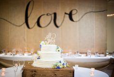 Buttercream wedding cake with fresh flowers on a handmade cake stand. Hand painted burlap backdrop. #rusticwedding #countrywedding #backdrop #rusticweddingcake #weddingcake