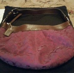 Coach hobo bag This bag is brand new, with tags Its authentic,  you can see by the picture, with the stamp they use. Its a beautiful wine color, and has darker purple C's All over it. There is a zipper pocket on back, and zipper pocket on the inside, and a couple of smaller pockets. The top of the purse, and the strap is made of a heavy leather. The rest of bag, is a thick cloth. Its a very nice hobo bag, with lits of room. The black bag comes with it. Make offers if u like Coach Bags Hobos