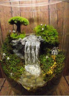 Очаровательный флорариум с водопадом в большой стеклянной вазе.