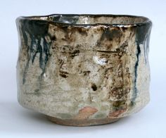 Pinched and carved tea bowl with ochre slip. blue pigment and sycamore ash glaze