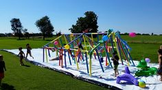 DIY slip 'n slide! My husband made this with a tent frame, a ton of pool noodles, water hoses, loofahs, sponges and a whole lot more. It was a huge success! #DIY #waterslide #homemade #slipnslide