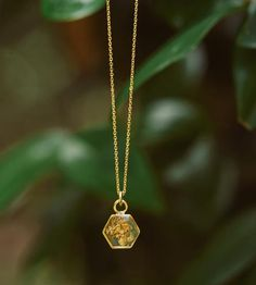 Every resin necklace makes the most of the semi-clear material by showcasing bright pieces of gold flake inside the pendant. This necklace includes a hexagon detail which was hand poured before any metallic leaf was added. Because it is made by hand, one step at time, no two resin necklaces are exactly alike.