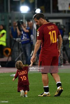 AS Roma's captain Francesco Totti walks on the pitch with his daughter Isabel during a ceremony following his last match with AS Roma after the Italian Serie A football match AS Roma vs Genoa on May 28, 2017 at the Olympic Stadium in Rome. Italian football icon Francesco Totti retired from Serie A after 25 seasons with Roma, in the process joining a select group of 'one-club' players. / AFP PHOTO / Vincenzo PINTO