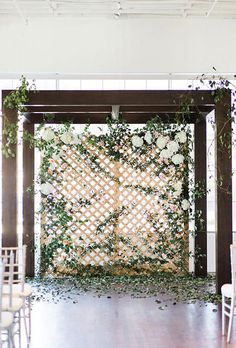 Brides.com: . Fresh hydrangeas, roses, and greenery woven through a freestanding trellis wall give the indoor ceremony venue a lush, overgrown-garden feel. Created by Bows + Arrows.