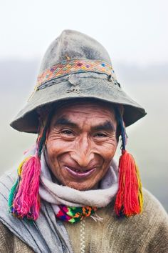 A Q'eros elder stands in the mist wearing traditional alpaca wool clothing and embroidery. The Q'eros, a traditional Quecha people living in the Peruvian Andes,  are considered the last direct descendants of the Incas.