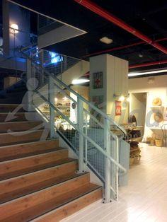 DÉCOR plataforma salvaescaleras instalada en interior de una tienda. La plataforma plegada se integra completamente en la barandilla de la escalera.