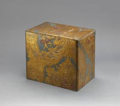 "6874 A kinkarakawa (gilt leather) box in gold, green and red damask motif covering a black lacquer kusuri-bako (apothecary box) of six drawers decorated with a single ume (plum) blossom beneath each of the circular handles. Holland/Japan 18th/19th century later Edo period Dimensions: H.12¼"" x W.14"" x D. 9"" (32.5cm x 35.5cm x 23cm) Kinkarakawa (gilt leather) was"