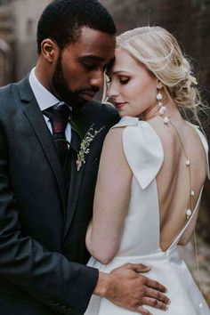 bride and groom cuddling back of brides dress has deep v neck at London wedding venue the Charterhouse