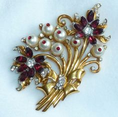This is a stunning 1940s gold tone flower bouquet complete with a bow. The red rhinestone and pearl bead flowers have clear rhinestones highlighting