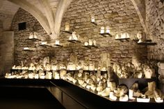 A striking display in the crypt of the Museum of Senlis (France) with fragments of statues lit from underneath shimmering like candles in the depth of the vaults.