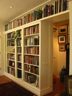 Modified IKEA bookcases: purchased three all-wood IKEA bookshelves. 2 large and 1 small in the middle.  Attach them all to the wall and sturdy them to one another and add trim and detail of shelf across the hallway door.    Fun project.